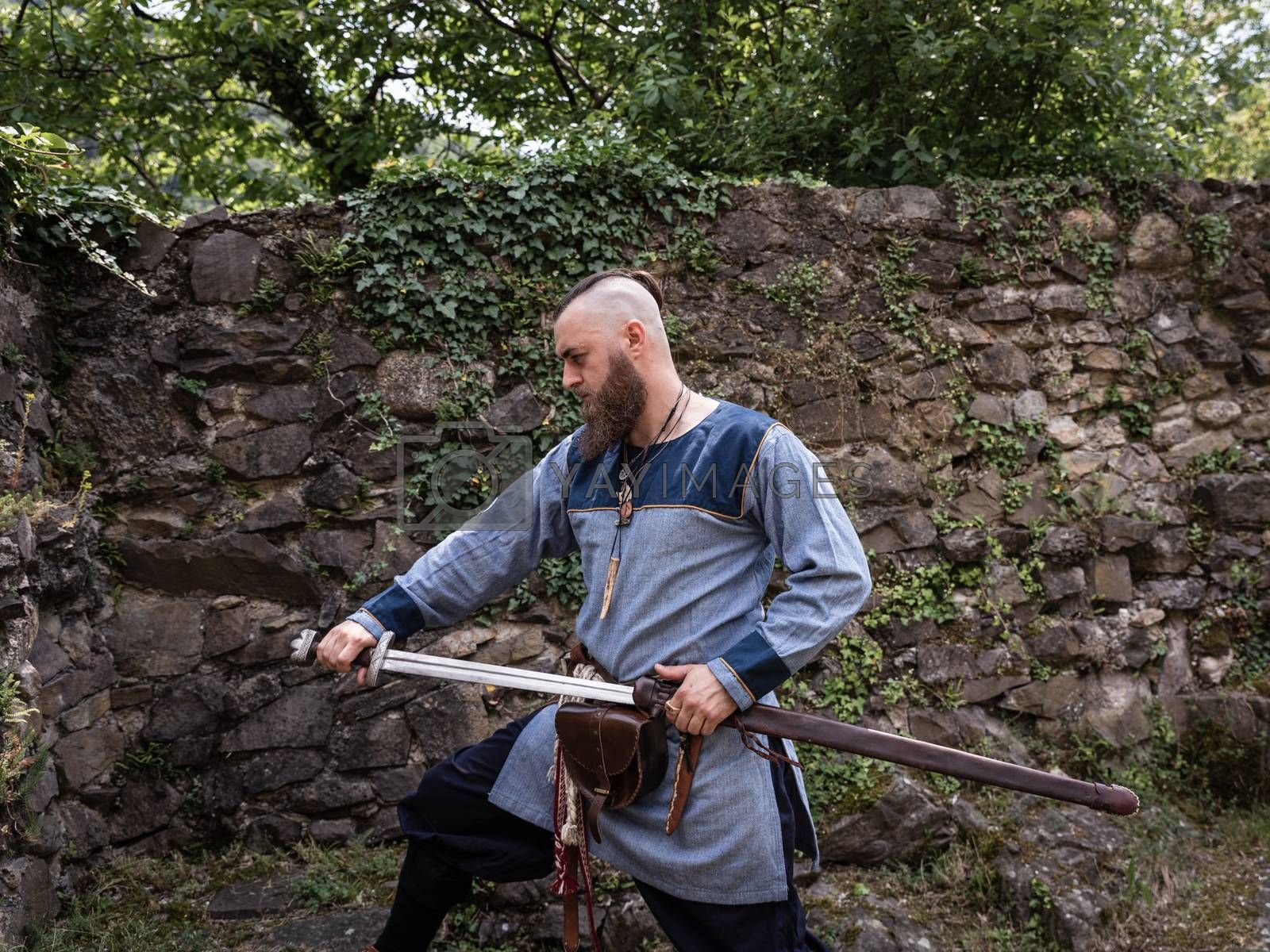 Medieval warrior draws sword from scabbard, Viking in traditional clothing