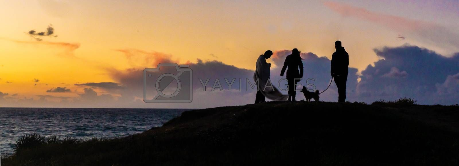 Romantic sunset of friends with dog on sea beach