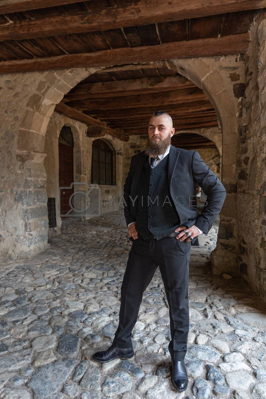 Man in elegant clothes poses under the arcades of a small village