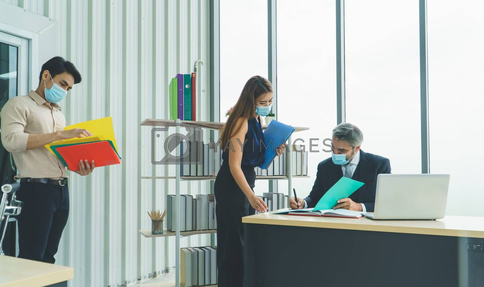 Business people wear a protective mask to work together in the company office. social distancing is the new normal. The concept of preventing the spread of coronavirus or COVID-19