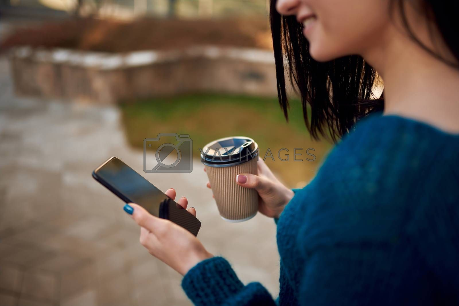 Close up of an unknown smiling female model looking on screen of a cellphone and drinking coffee outdoors