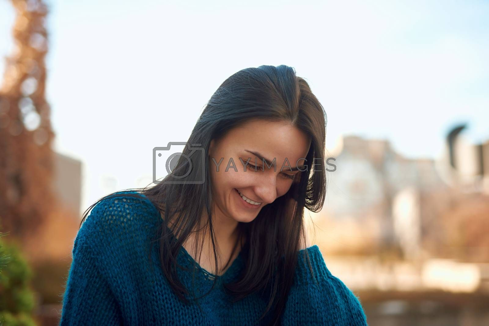 Young beautiful woman looking down with happy smile while tidying up her hair with hand on defocused background of city street