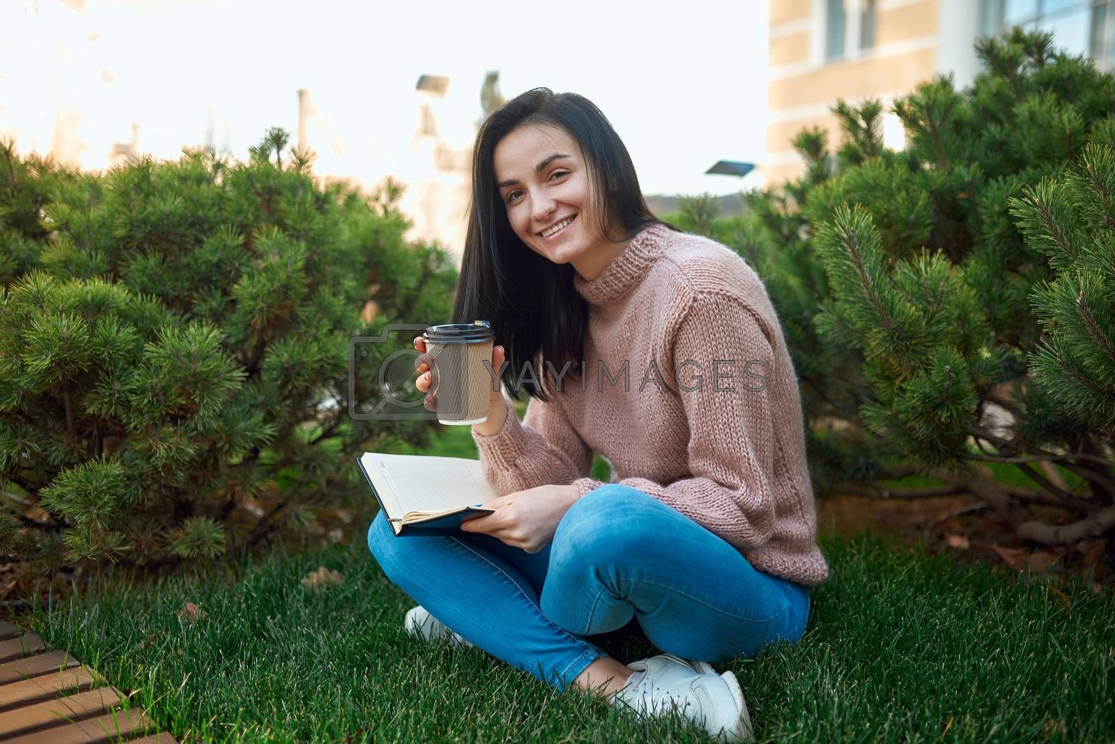 Cheerful young lady with paper glass of coffee in hands holding her memo book on knees while sitting on a cosy green lawn