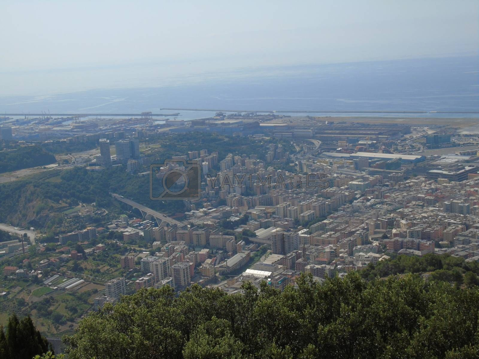 Genova, Italy – 07/30/2020: Beautiful scenic aerial view of the city, port, dam, sea, Cristoforo Colombo airport runway, containers shipping terminal, Pra, Voltri, and Sestri promontory from Monte Gazzo
