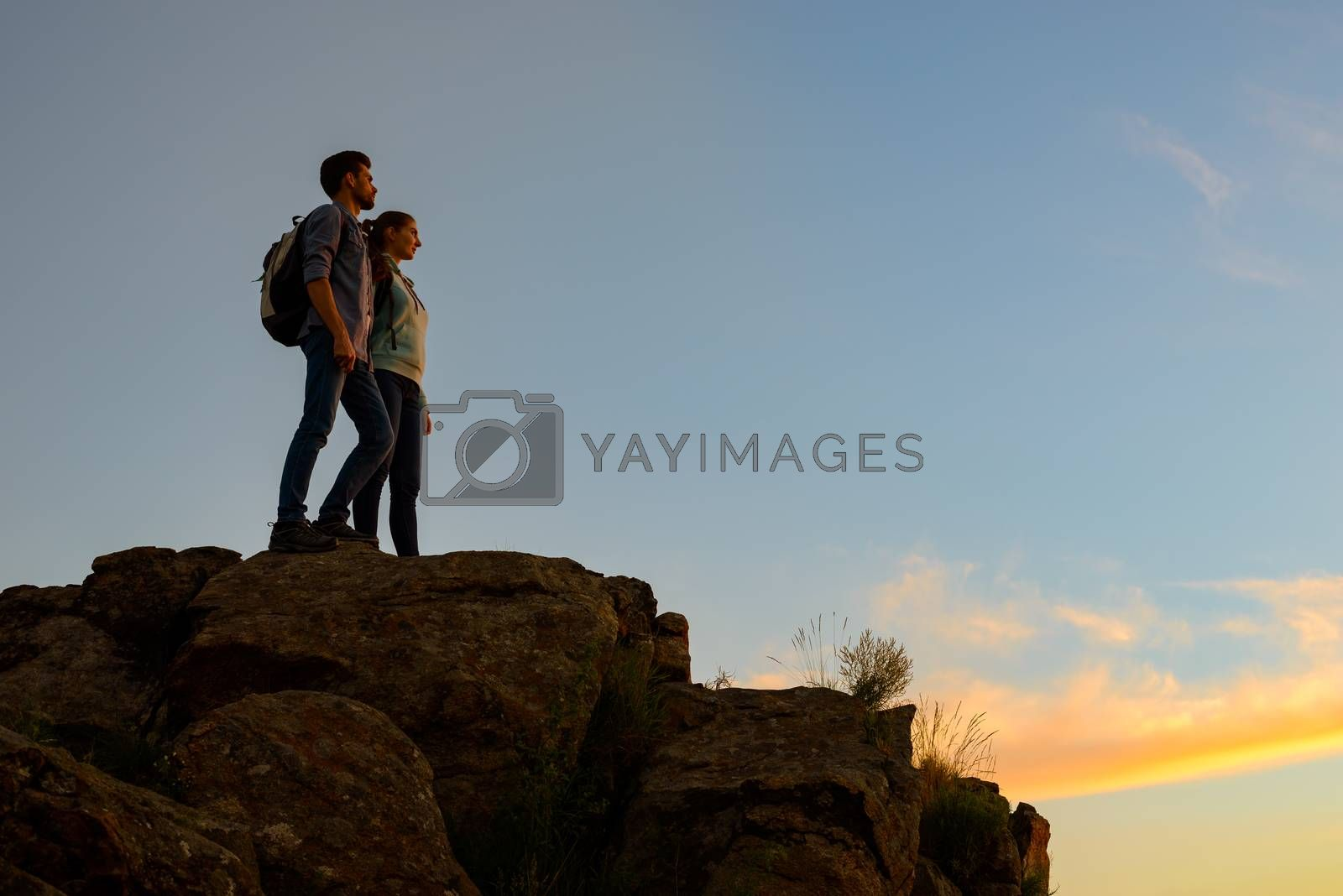 Couple of Young Travelers with Backpacks Standing on the Top of the Rock at Summer Sunset. Family Travel and Adventure Concept.