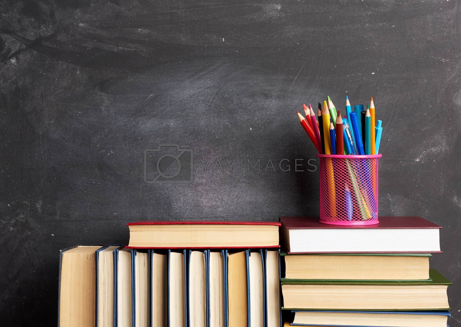 stack of various books, stationery on black chalk board background, back to school, copy space