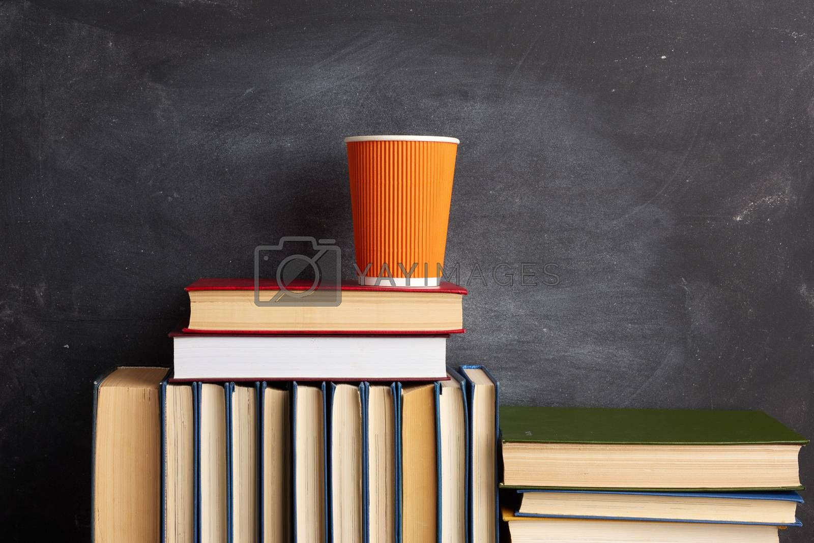 stack of various books and an orange disposable cup with coffee on a black chalk board background, close up