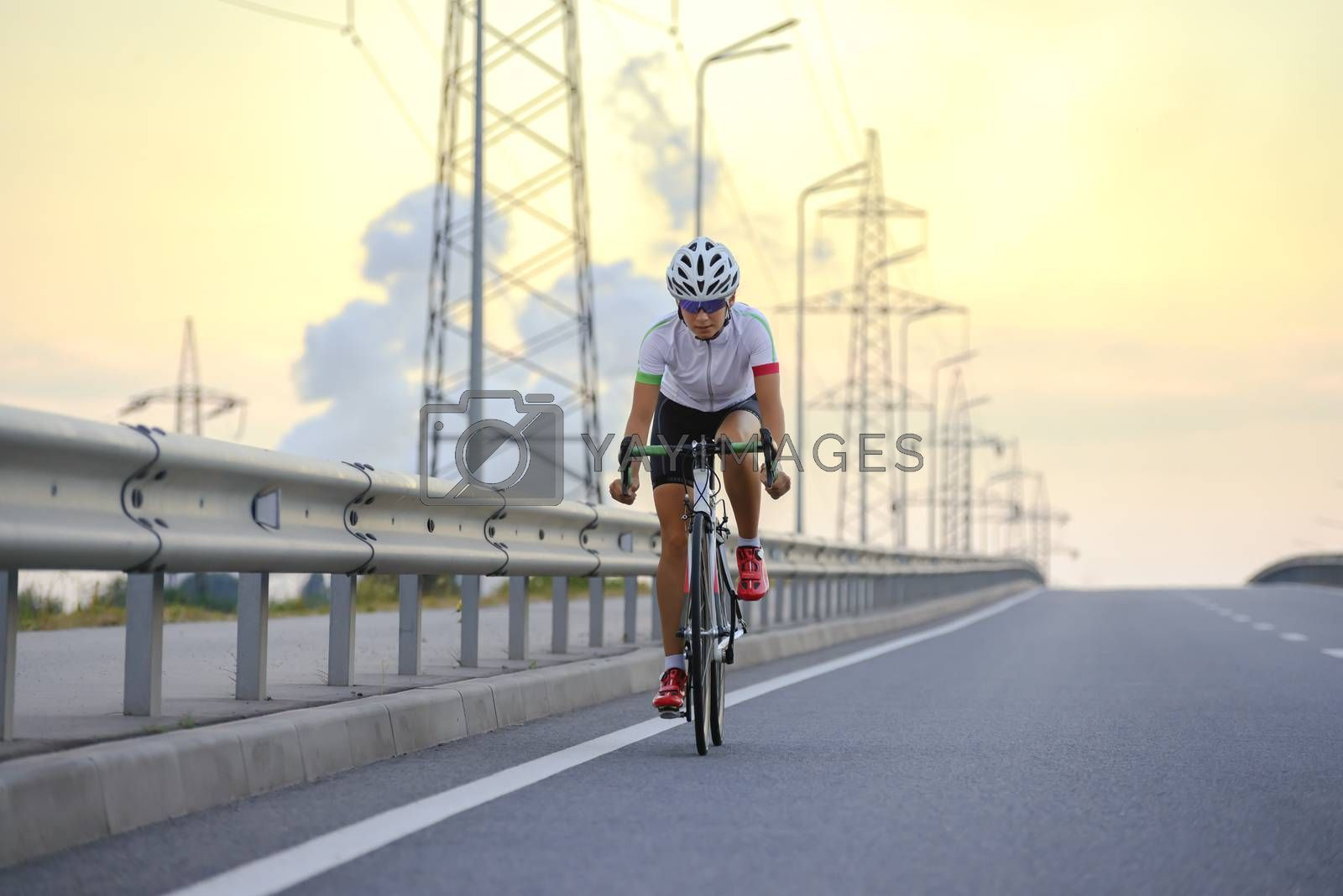 Young Woman Cyclist Riding Road Bike on the Background of Sunset Sky. Adventure, Travel, Healthy Lifestyle and Sport Concept.