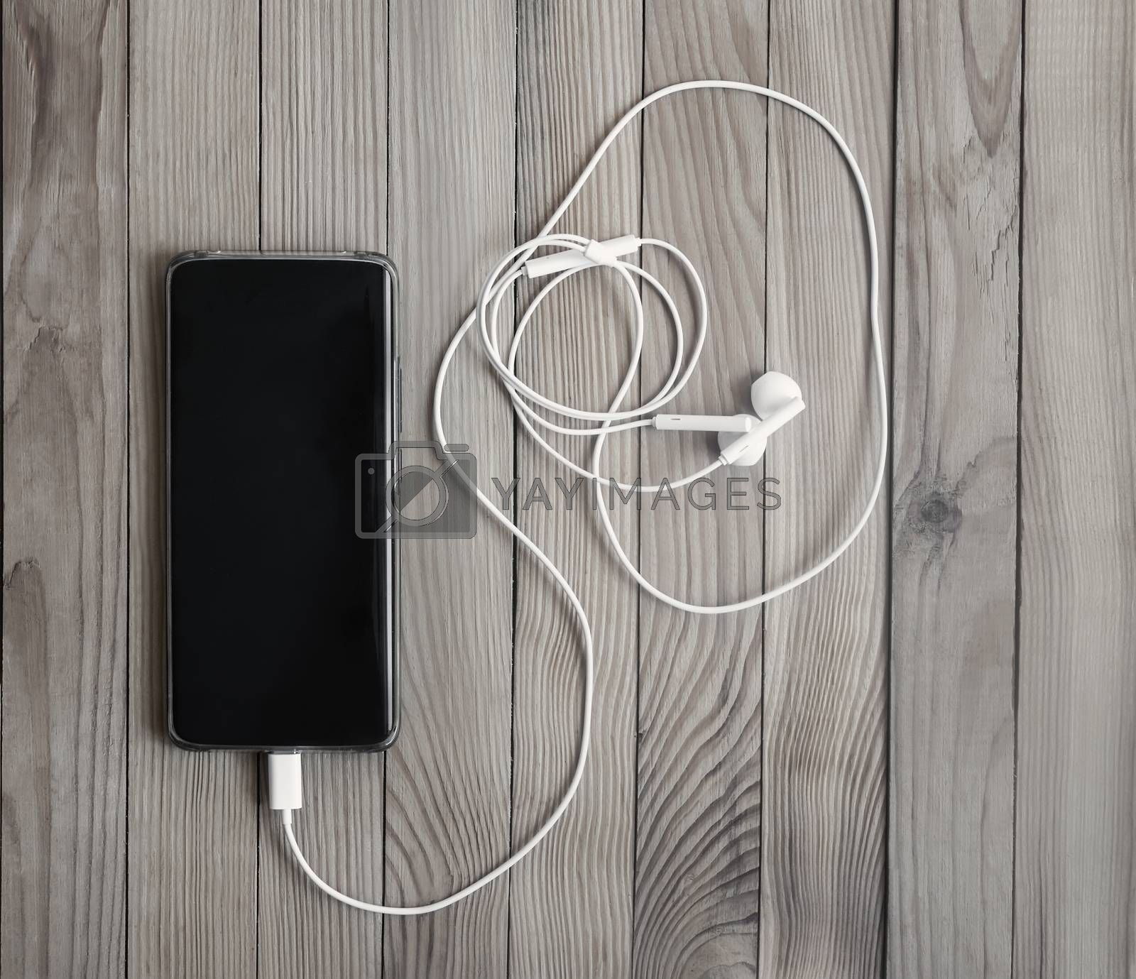 Modern smartphone and headphones on the background of a wooden table. Close-up, top view, copy space