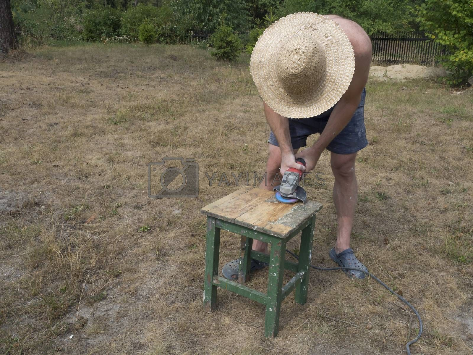 The man in straw hatworking with eletric grinder machine, tool for grinding and polishing the surface, renovating and polishing old wooden small table, outside on his garden