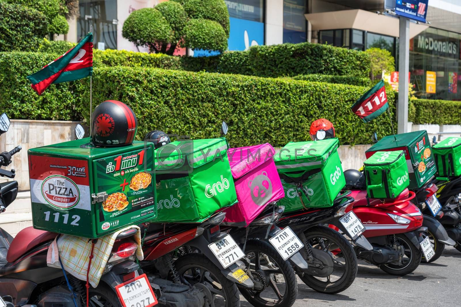BANGKOK, THAILAND - APRIL 2020 : Various food delivery box on the motorcycles include Grab Food, Food Panda and Pizza at Food delivery service point on April 17, 2020, Bangkok,Thailand, Covid outbreak