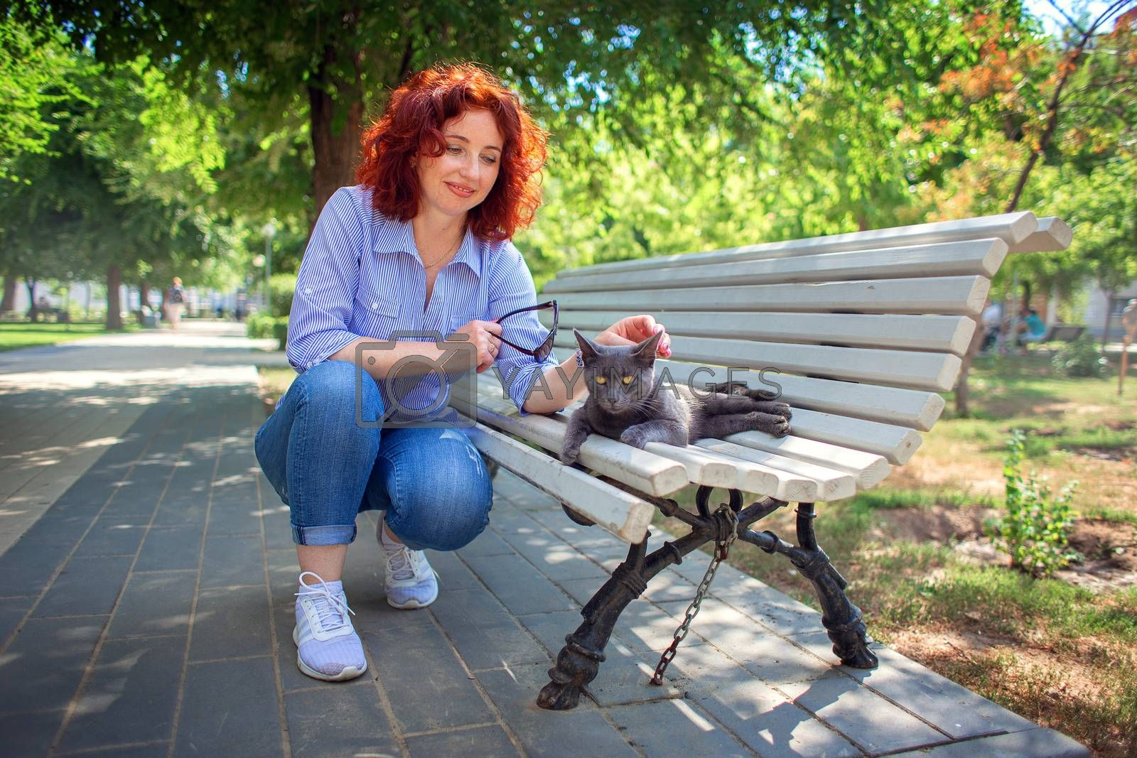 A red-haired curly girl in the park on a bench stroking a gray street cat. Love to the animals