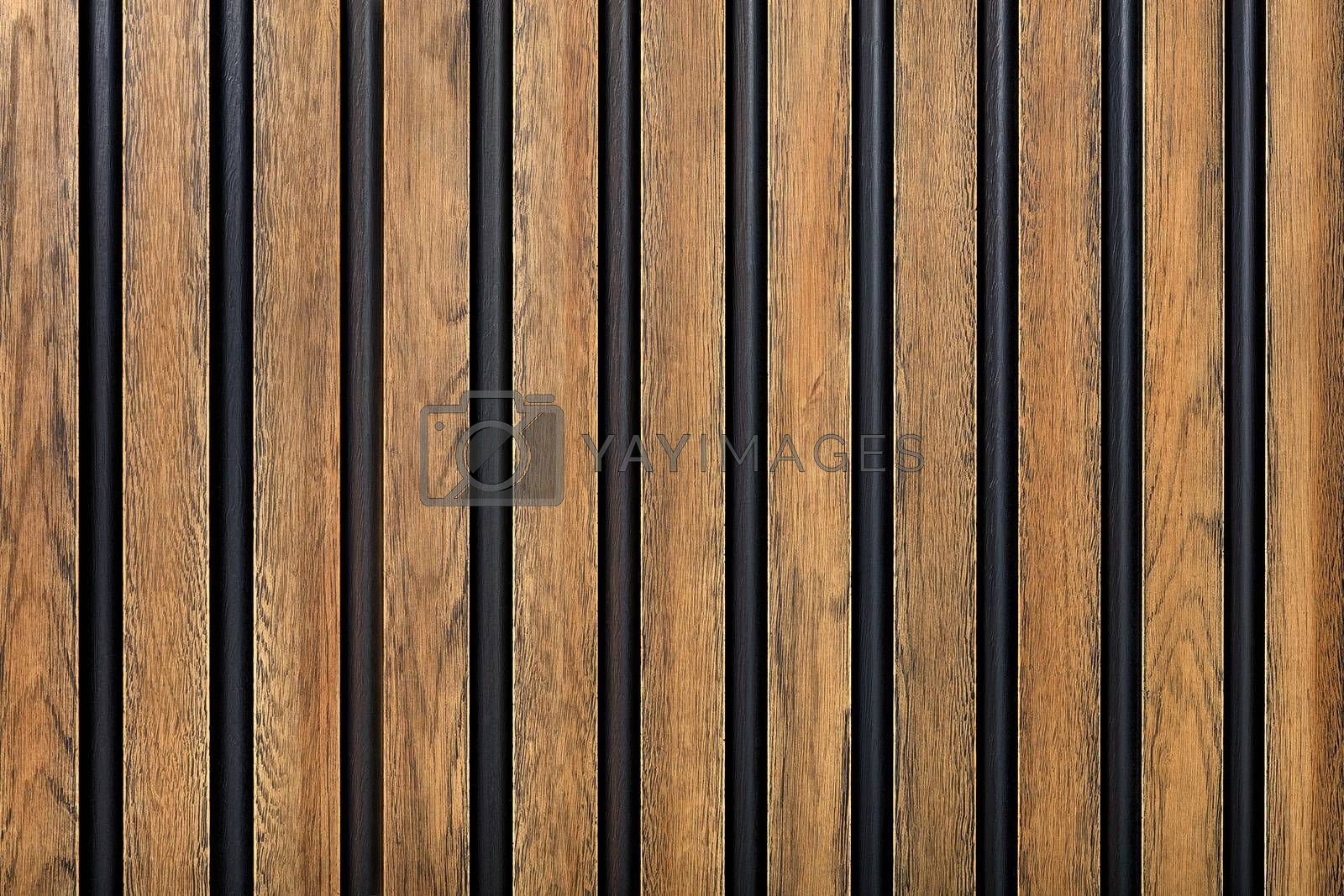 A wooden fence made of vertical decorative planks with a pronounced texture of light brown color with black spaces.