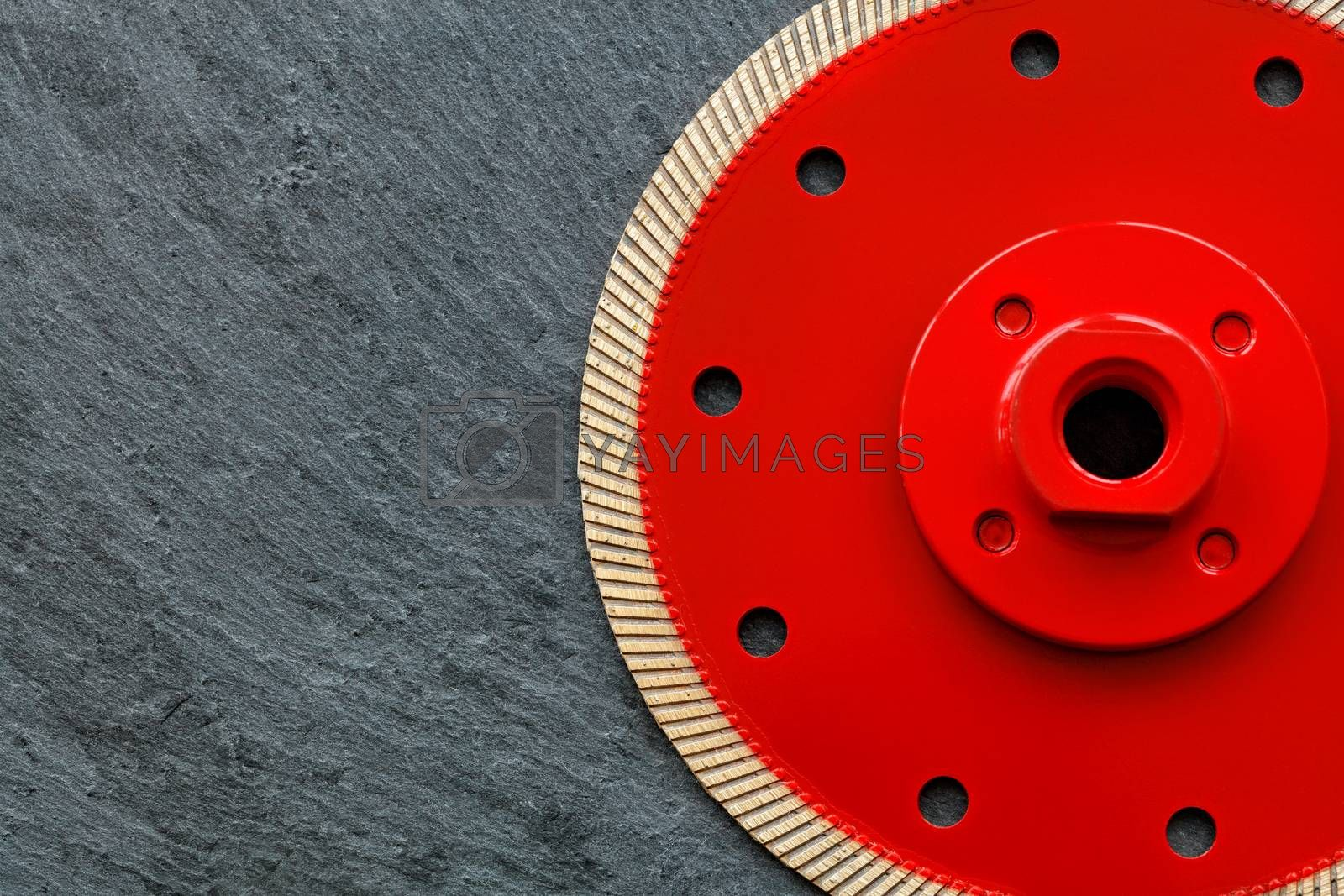 Cutting diamond professional blade of red color, a thin blade with a flange is used for precise cutting of the material against the background of gray granite, image with copy space.