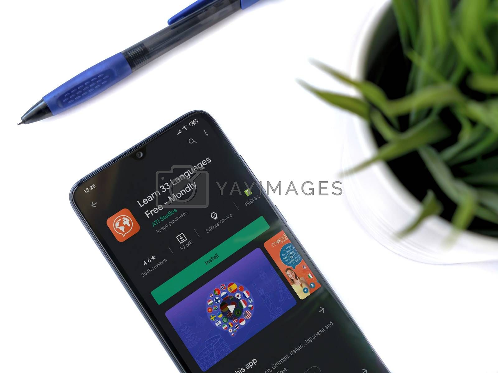 Lod, Israel - July 8, 2020: Modern minimalist office workspace with black mobile smartphone with Mondlay - Language learning app play store page on a white background. Close up top view flat lay.