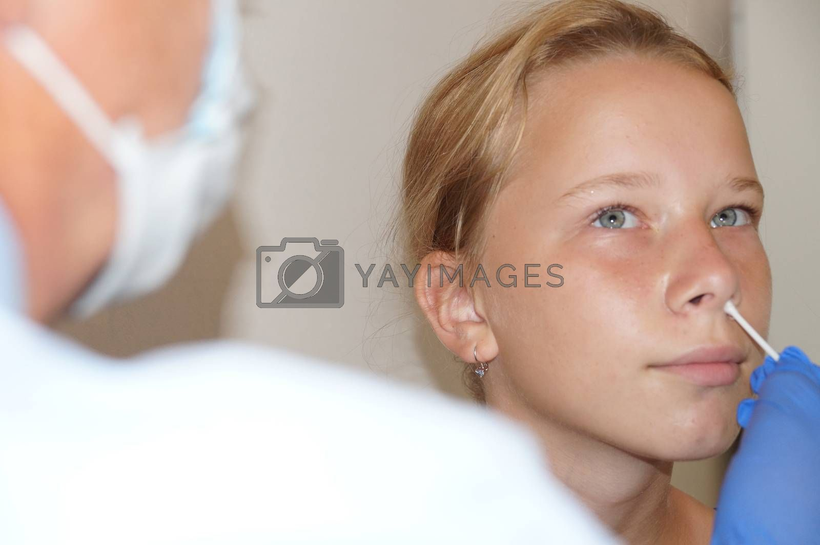 the doctor takes a test for coronavirus from the girl's nose.