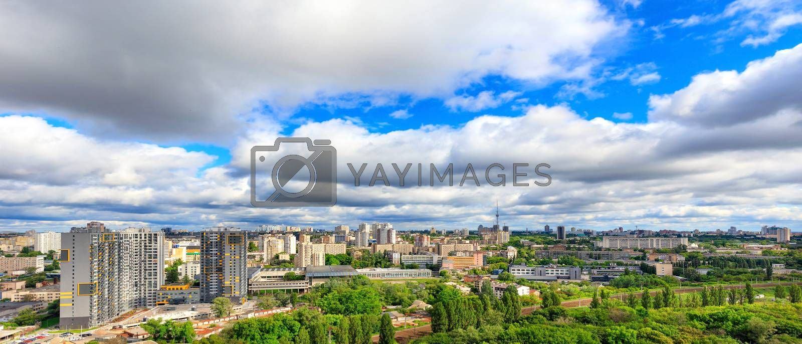 Large low clouds fill the sky over a sunny city with tall apartment buildings and green parks in a panorama with cityscape and horizon.