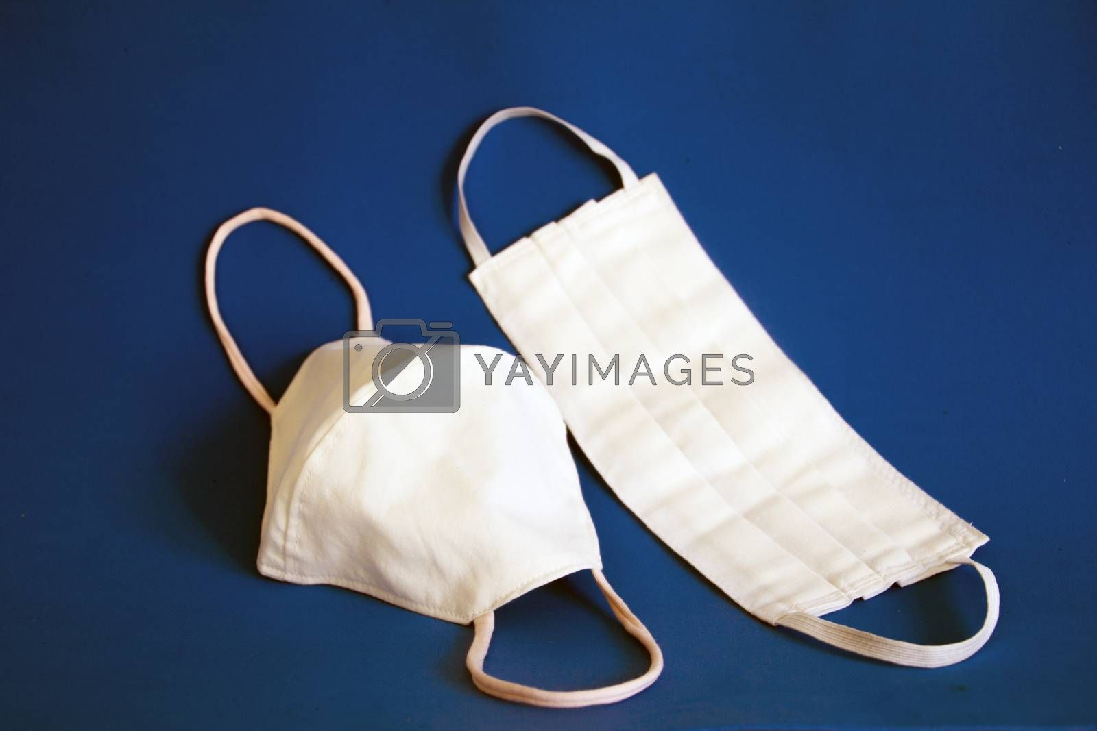 two diferent kind of homemade protection masks for covid-19 with a blue background
