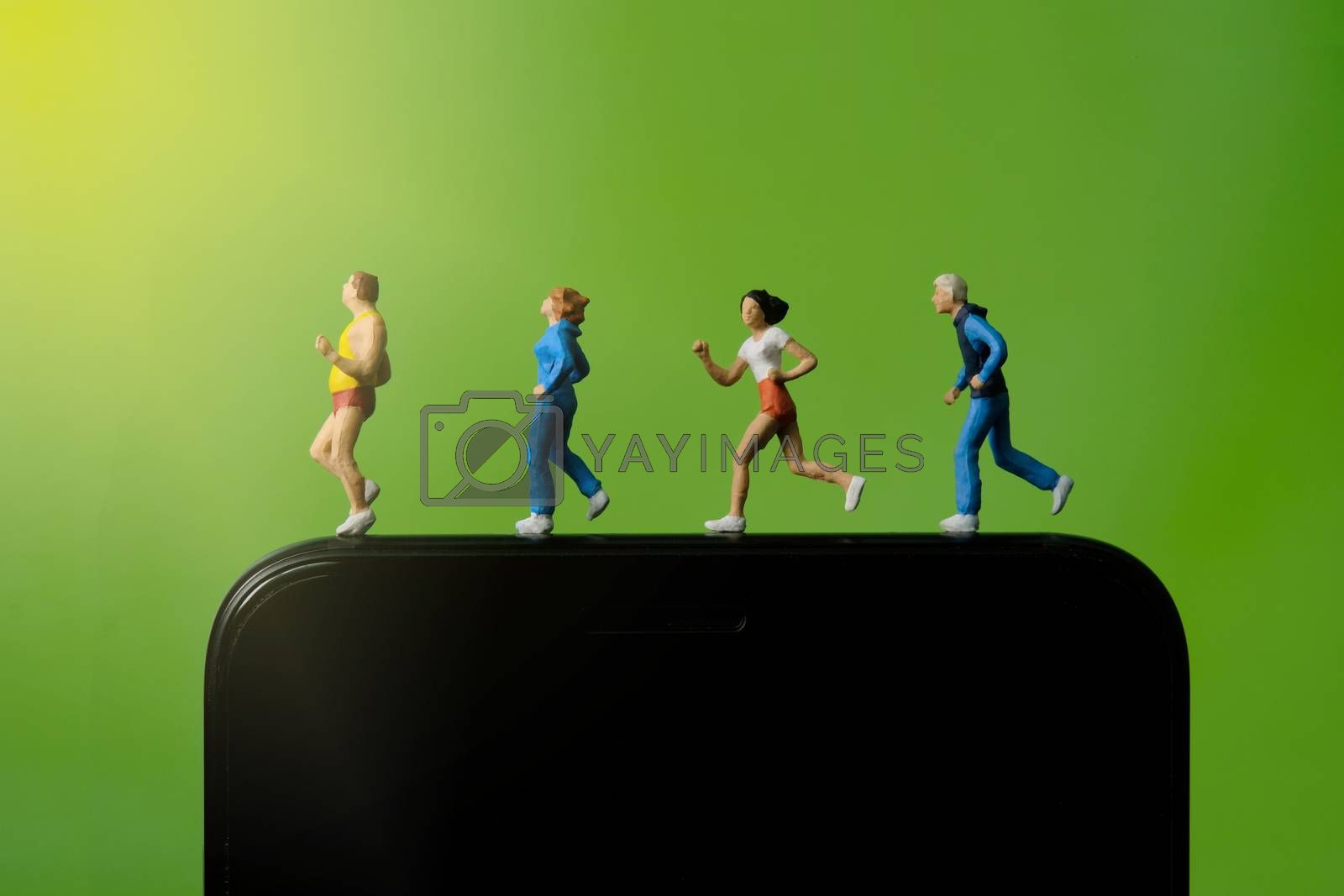 Running and jogging tracking app concept. A family running above smartphone. Miniature people figure photography.