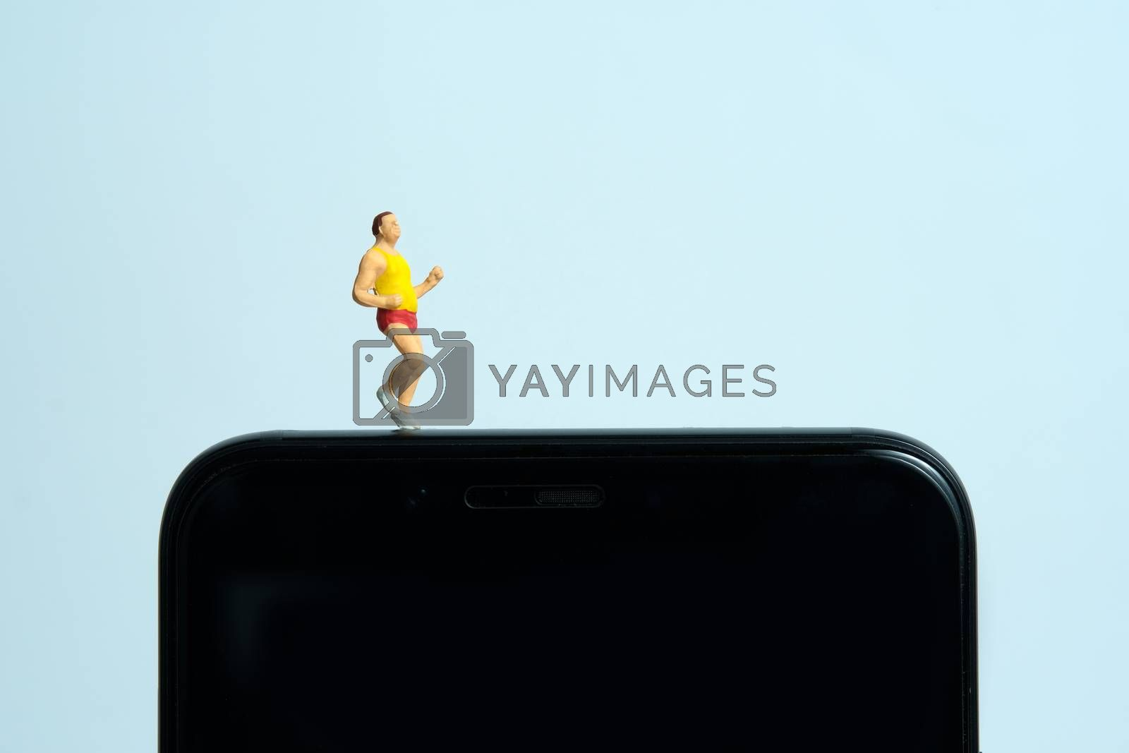 Running and jogging tracking app concept. A fat men running above smartphone. Miniature people figure photography.