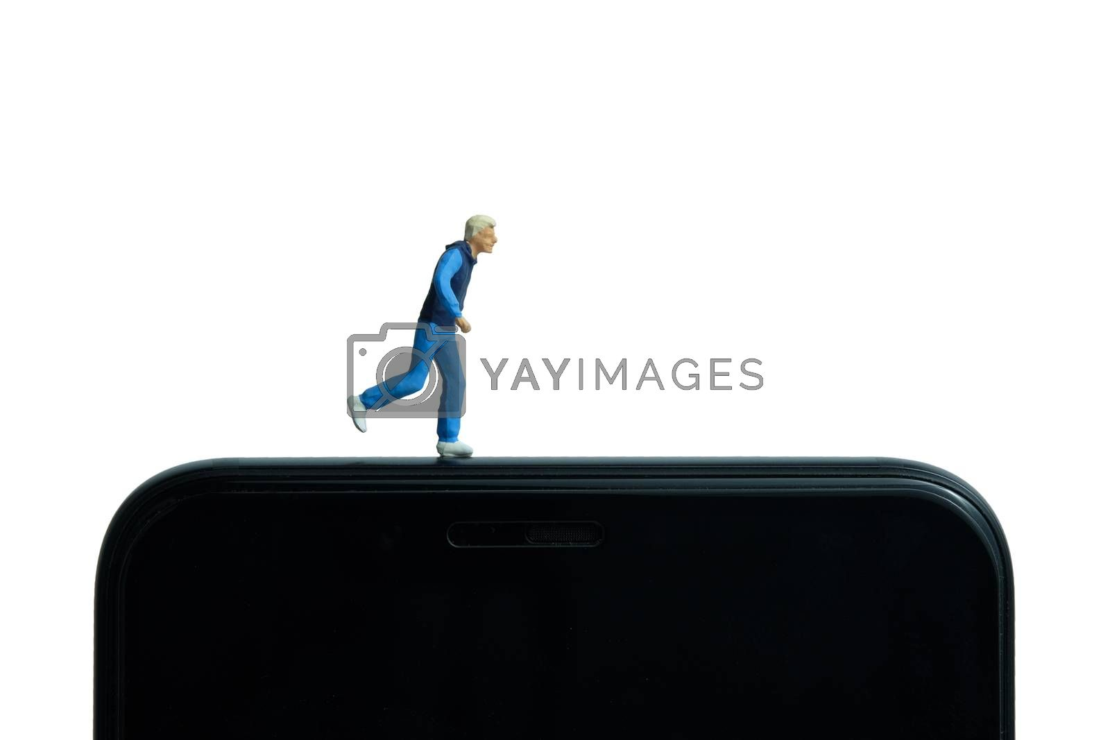 Running and jogging tracking app concept. A men running above smartphone. Miniature people figure photography.