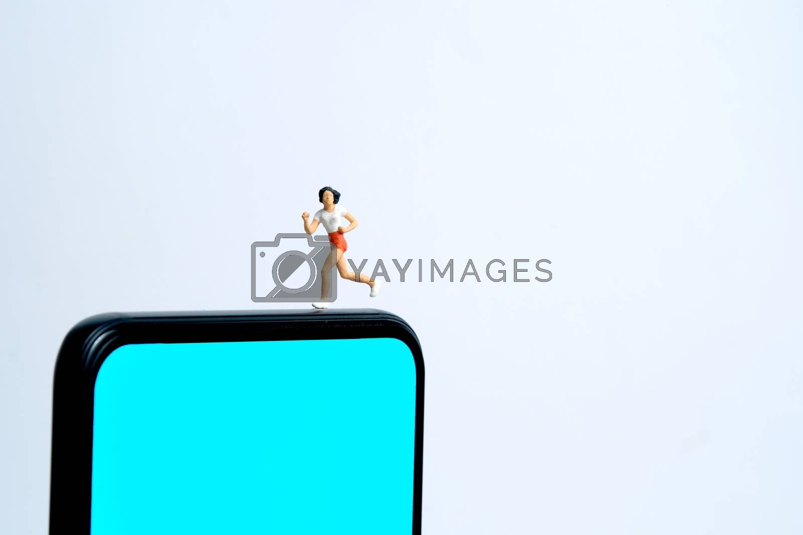 Running and jogging tracking app concept. A women running above smartphone. Miniature people figure photography.