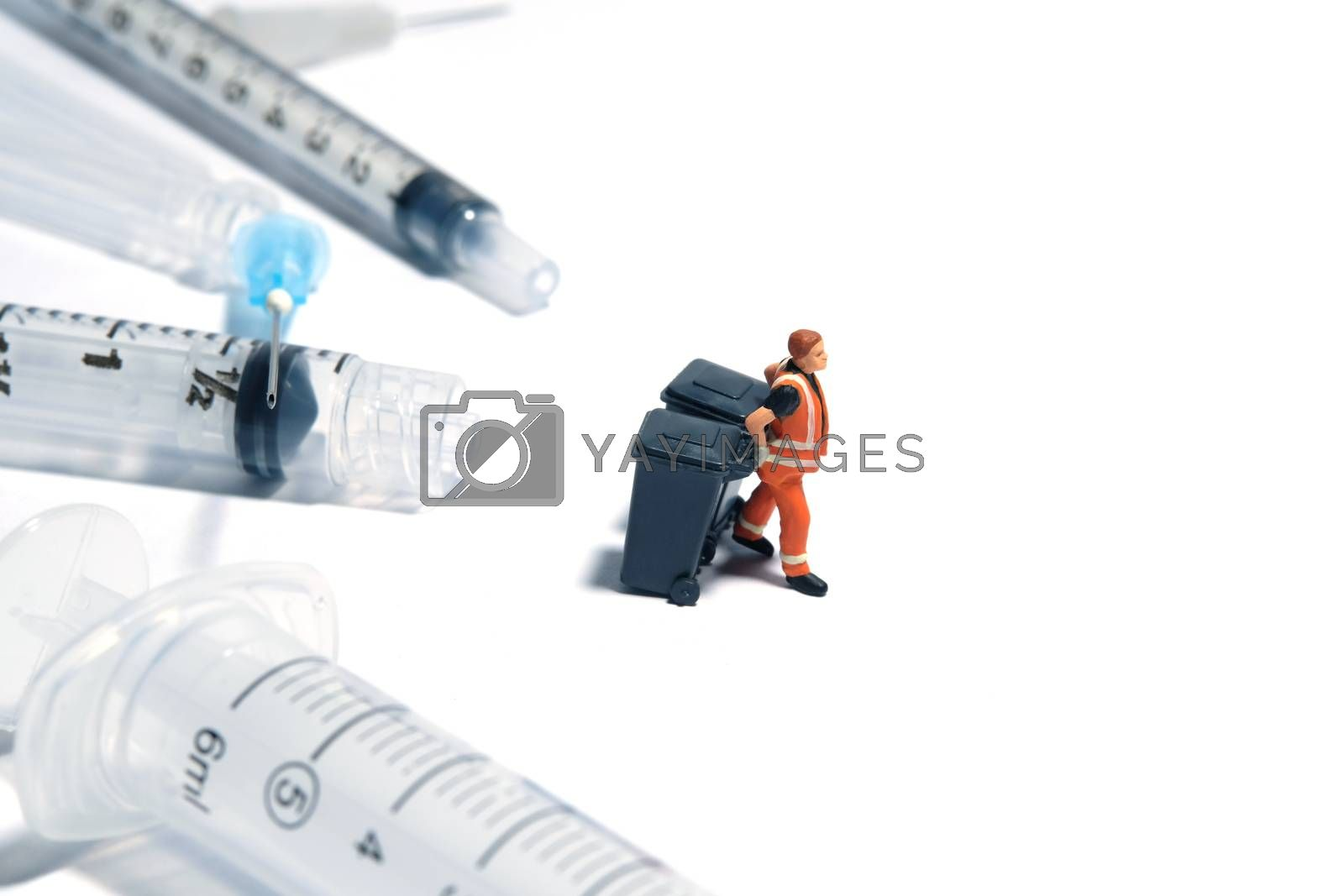 Cleaning workers pulling trash bin, in front of syringe that has been used. Medical waste conceptual photo. Miniature people photography.