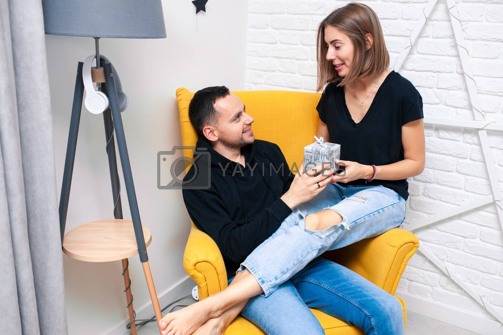 Portrait of couple young in a cozy room. A man sits on a yellow chair. A woman sits on the lap of a man and holds a gift Christmas family holidays. Modern style interior.