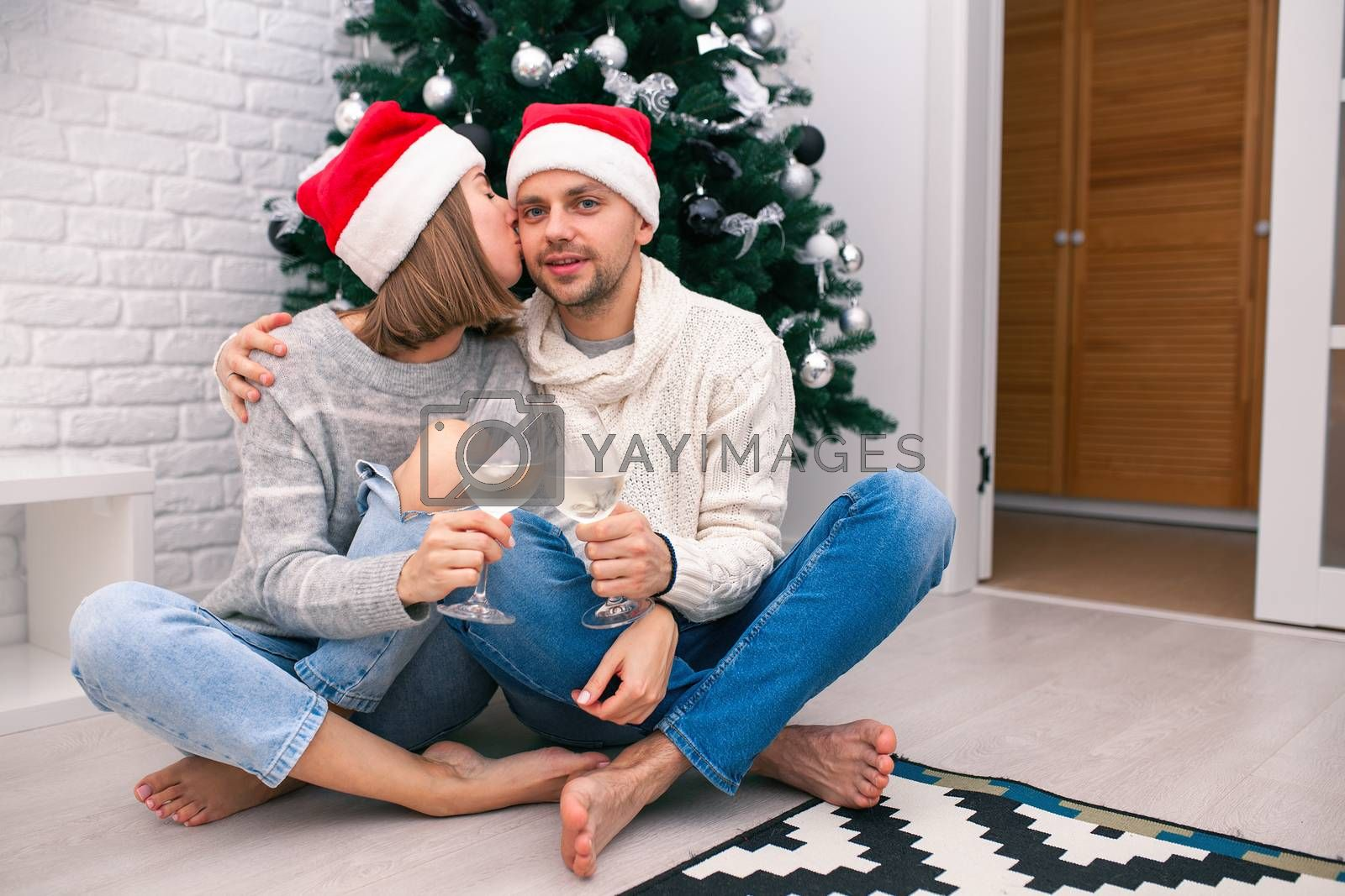 Young happy couple in Christmas hats near a Christmas tree kissing, holding glasses of wine. New Year celebration. Happy New Year Family Concept. Christmas for two
