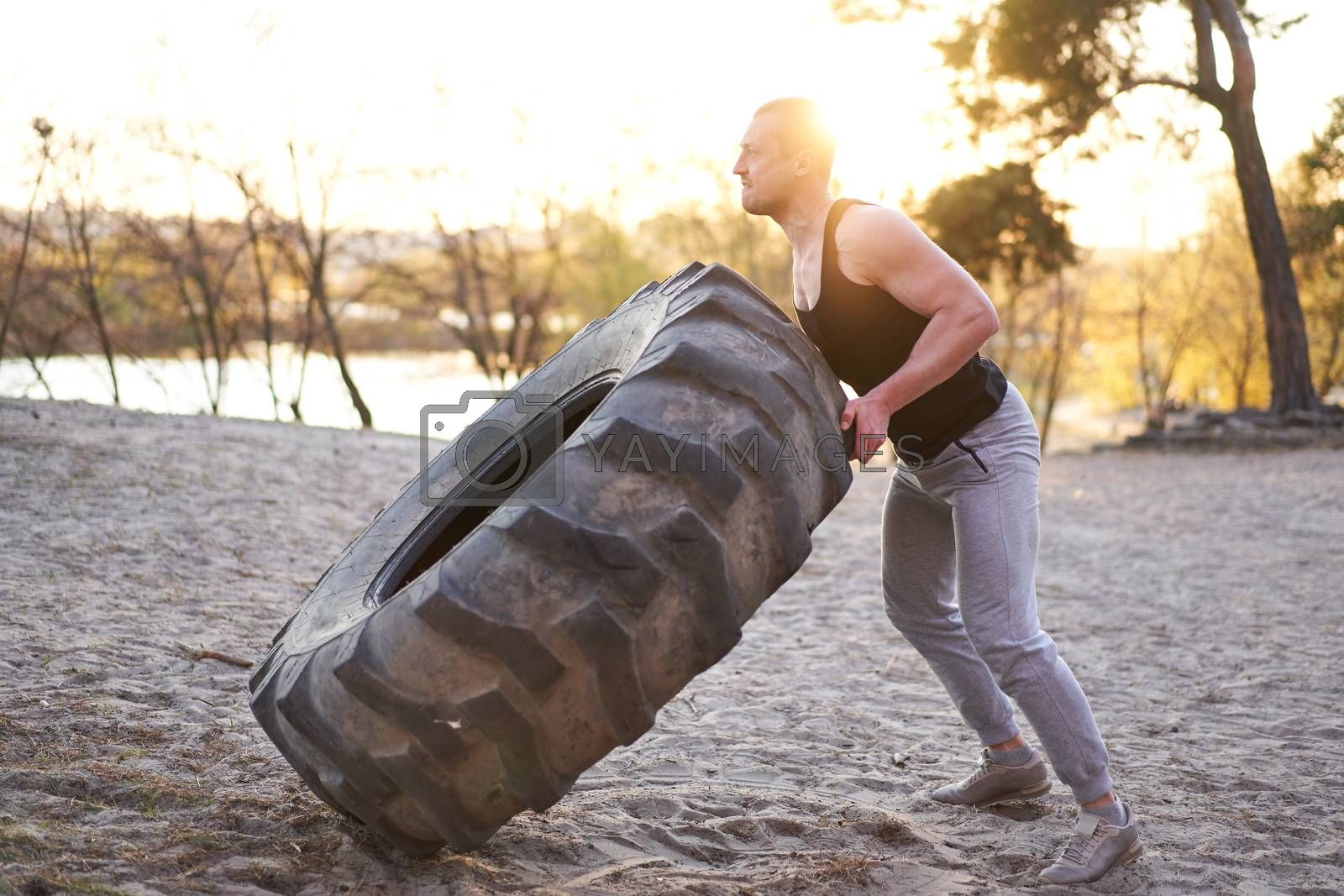 Strong man training workout lifting large tire outdoor DIY gym. Sportive young adult caucasian guy flip big wheel on nature. Handmade equipment sport exercising helthy lifestyle concept