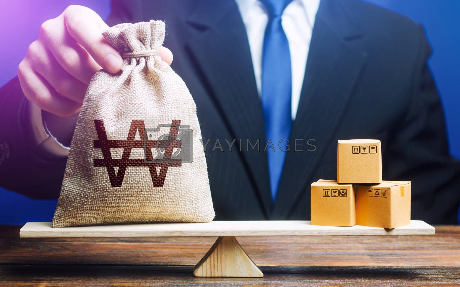 South korean won money bag and boxes on scales. Trade balance and purchasing power. Import and export duties, profit from the sale of value added goods. Economic and industrial development. VAT