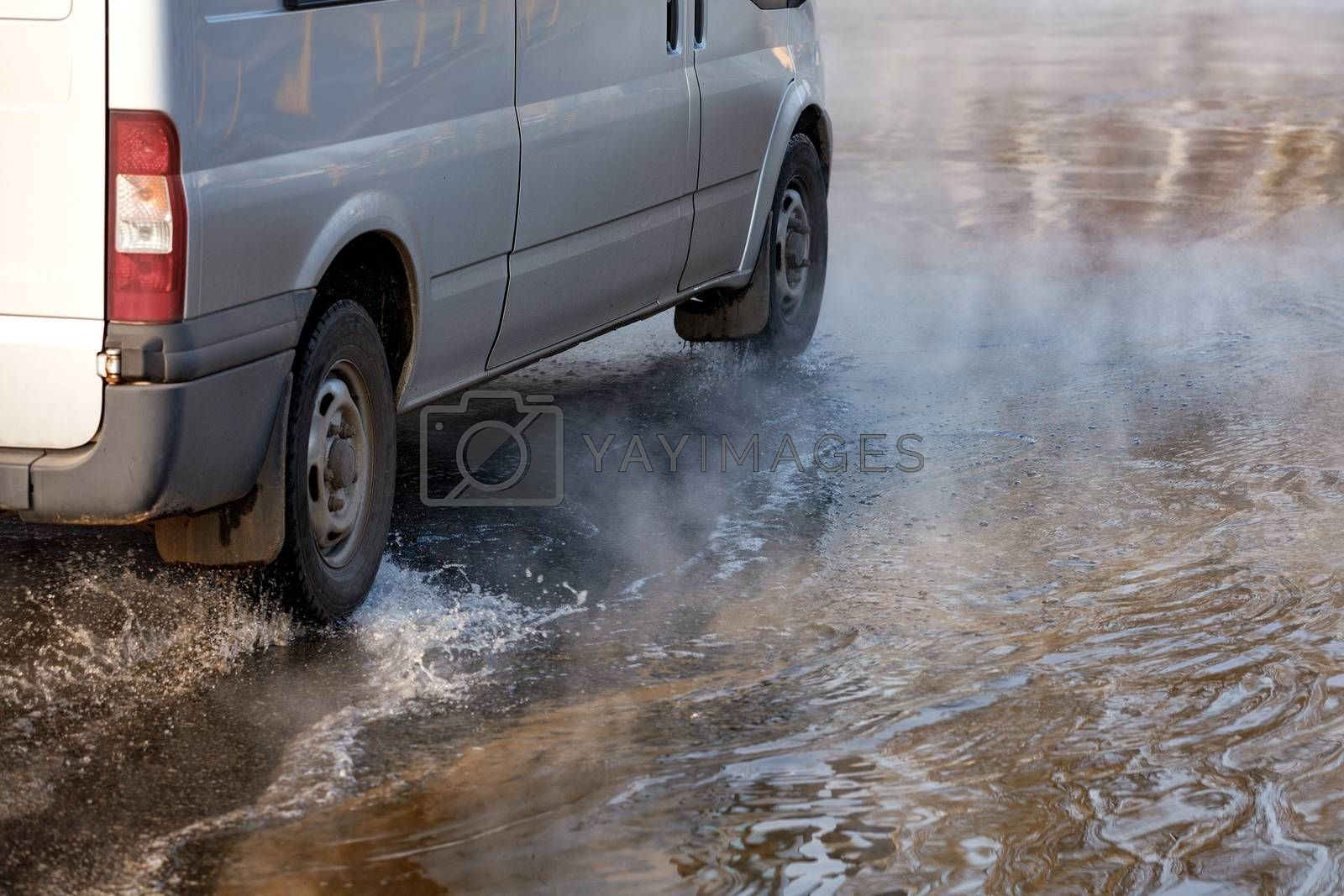 An accident on a heating main, a break in a pipe with hot water, a car driving along a flooded road, water vapor forms a smokescreen on the asphalt, an image with copy space.