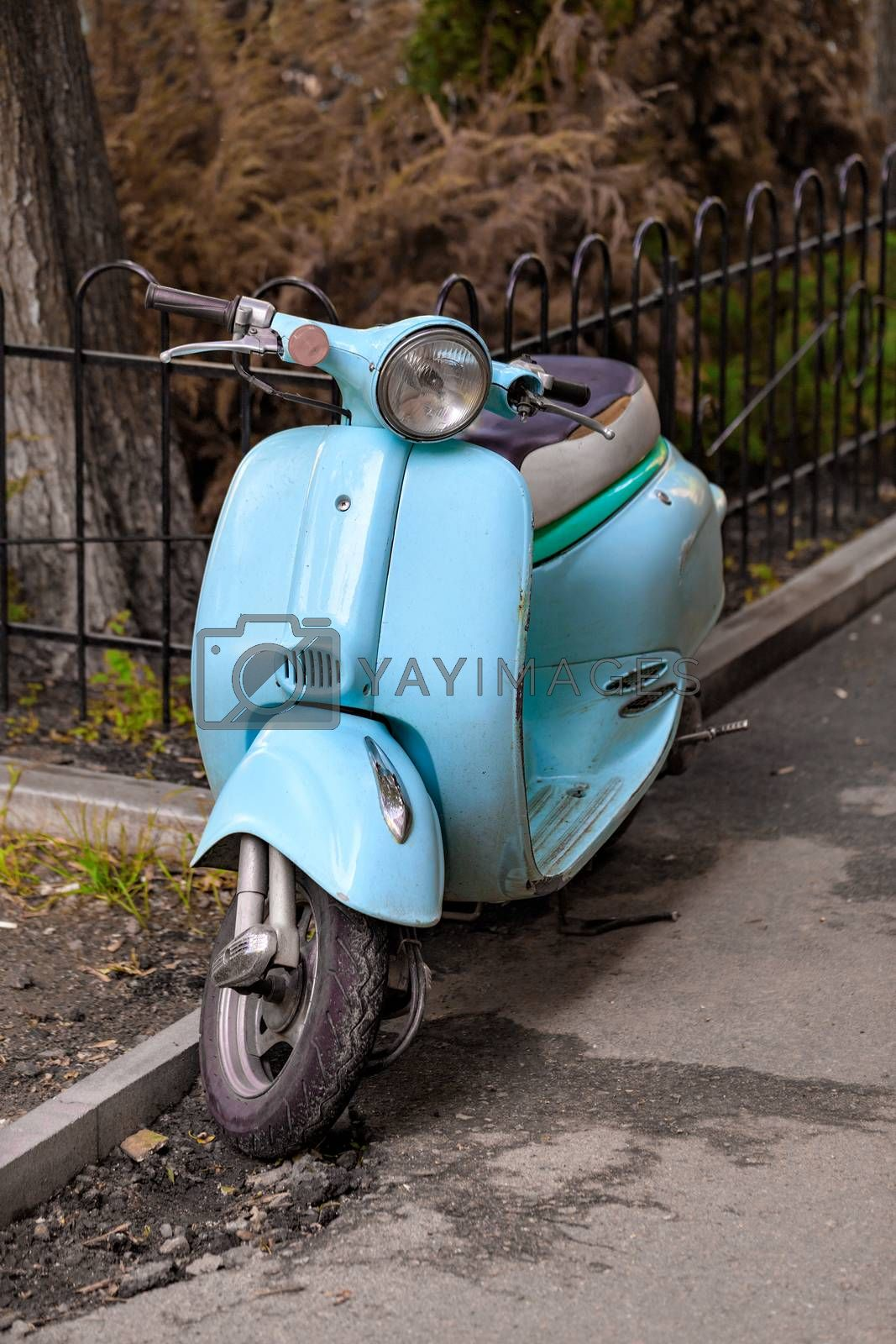 Light blue retro scooter parked on the old street of the city. Vintage style. Copy space.