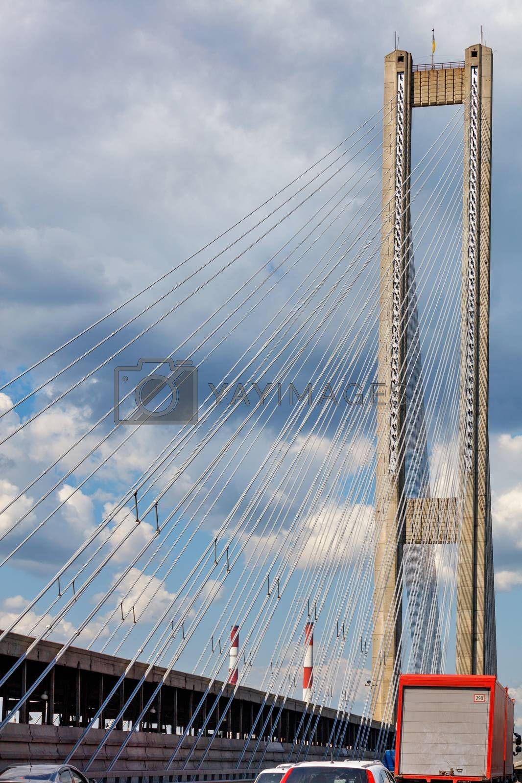 Cable-stayed South Bridge in Kyiv against the background of a stormy cloudy sky, traffic on the bridge, Ukraine.