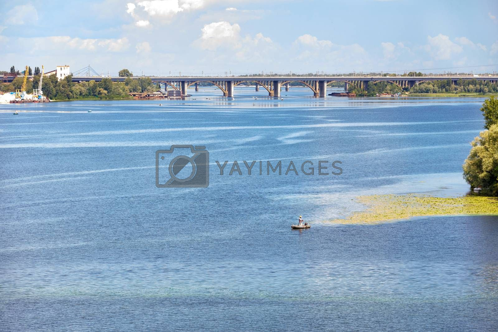 The water surface of the wide Dnipro River in the foreground, a lone fisherman on an inflatable boat in the middle, road bridges across the river on the horizon, copy space.