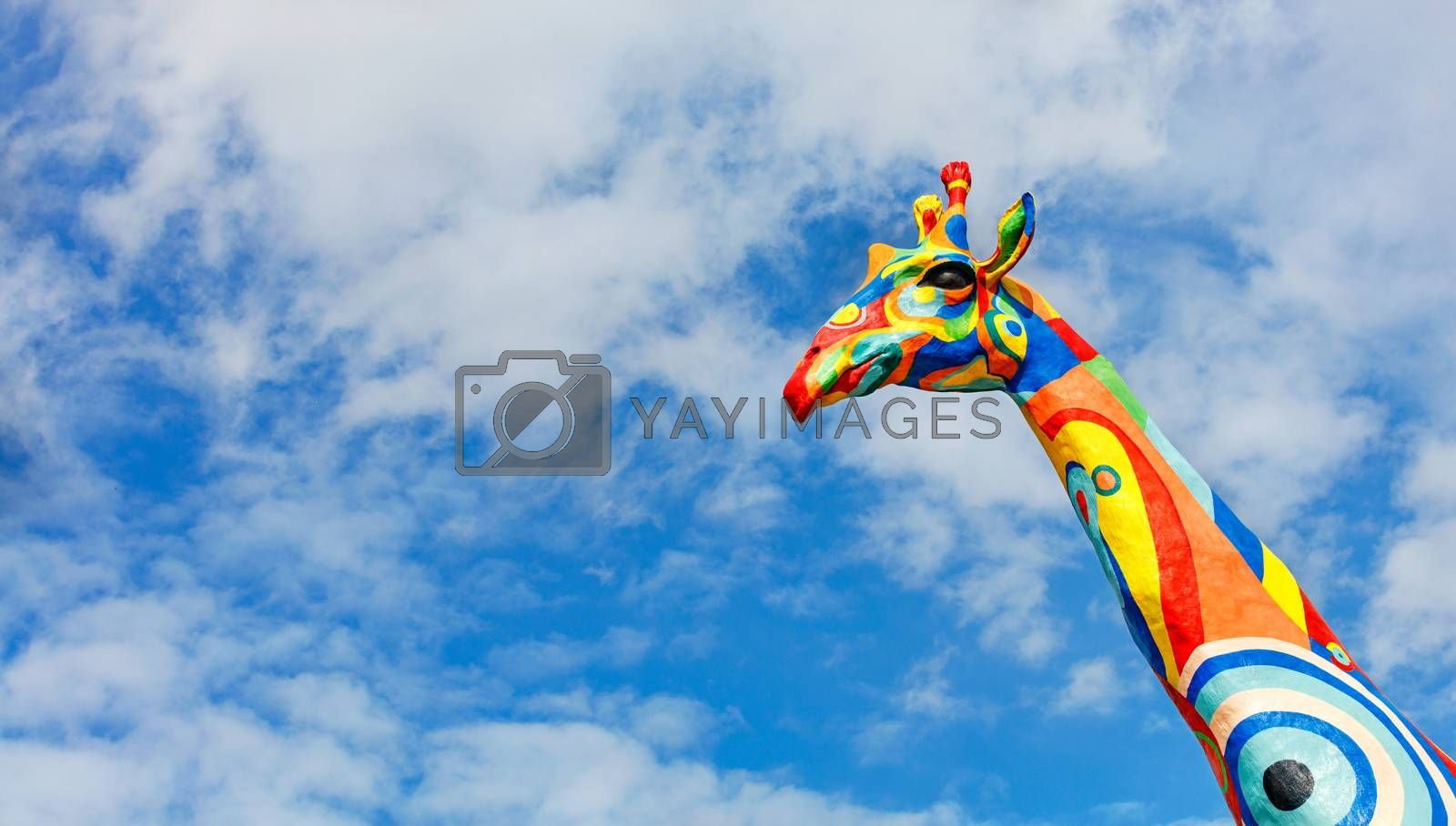 Painted cheerful giraffe head against a blue, slightly cloudy sky in sunlight, copy space.