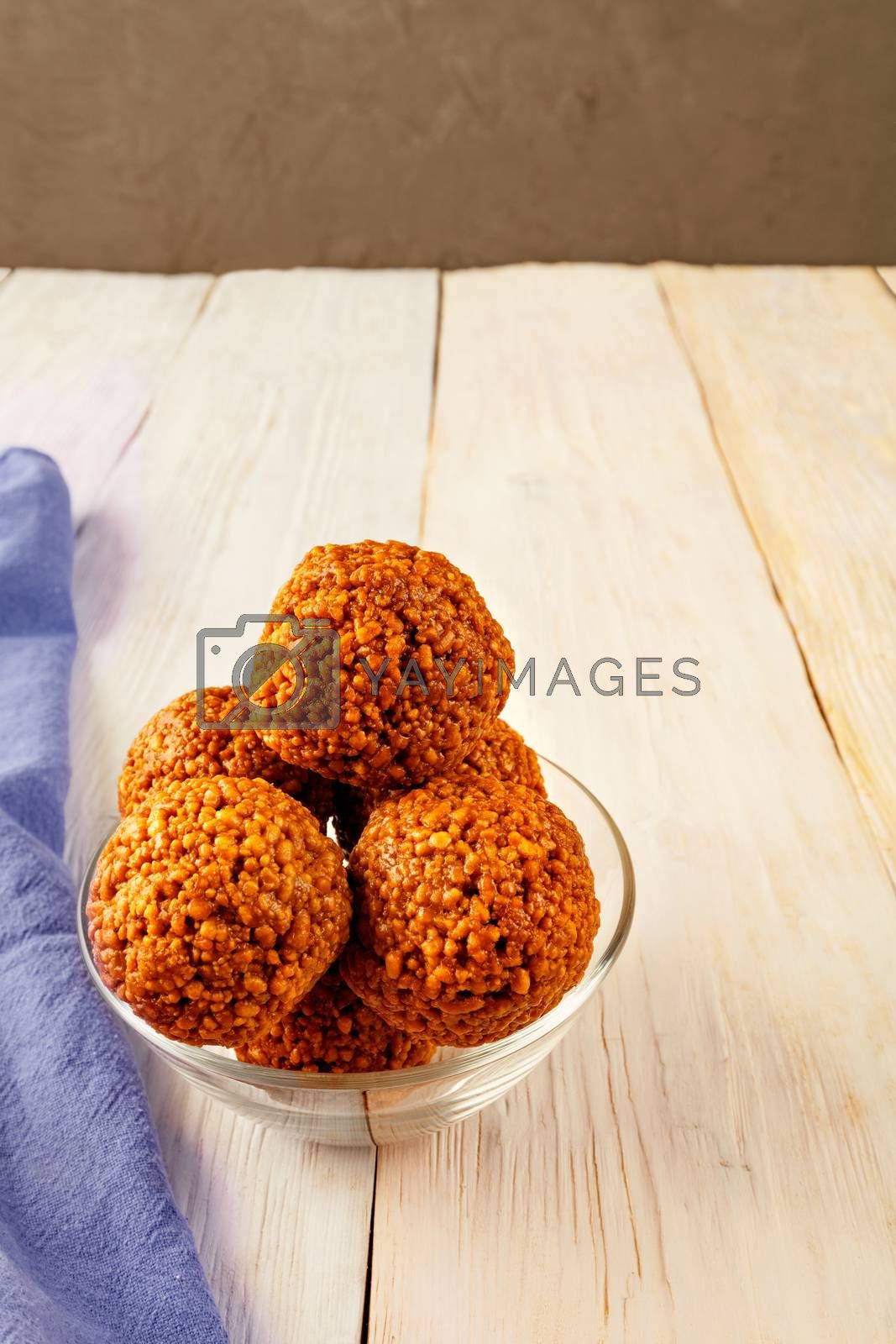 Homemade energy balls with walnuts and honey, light wooden surface and glassware. Rustic style. Vegan raw snacks. Healthy sweet food. Copy space, vertical image, close-up.