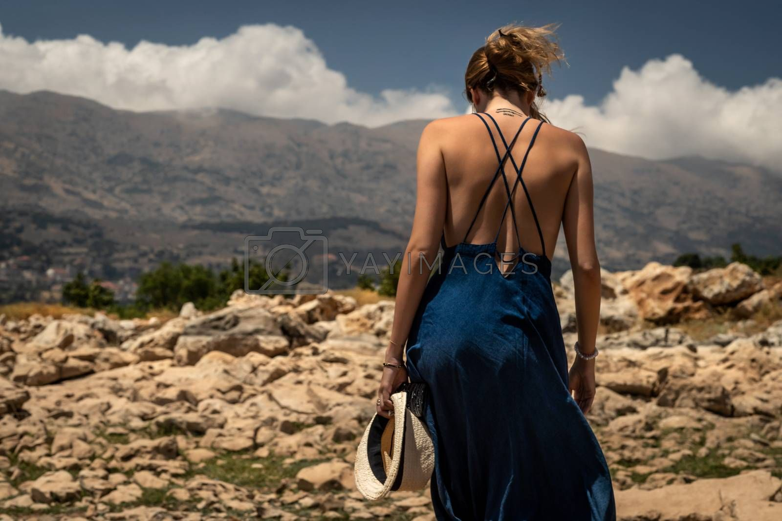 Back Side of a Beautiful Young Woman Standing on the Top of the Mountains. Enjoying Amazing Mountainous View. Happy Peaceful Summer Vacation.