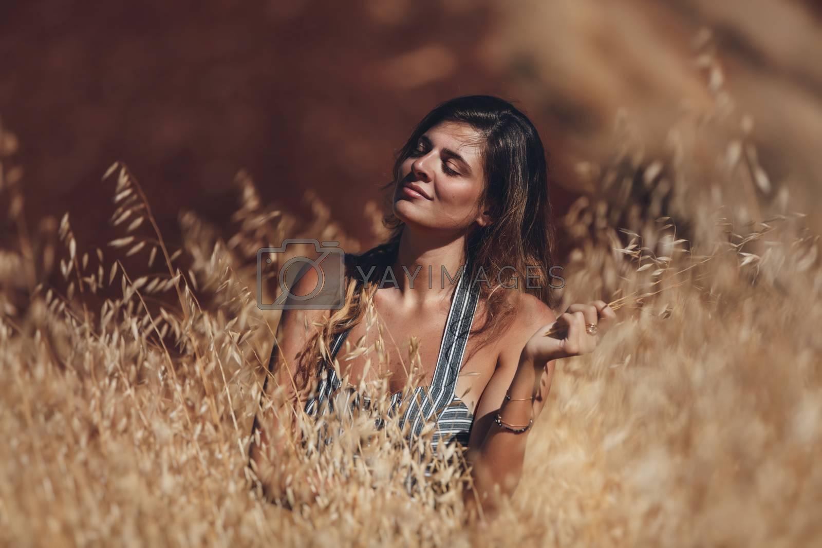 Portrait of a Calm Beautiful Female Model. Golden Wheat Field. Girl Enjoying Sunny Day.