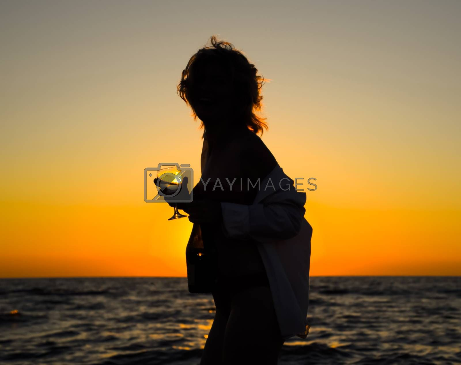 girl on a sunset background with a glass of champagne at sea.