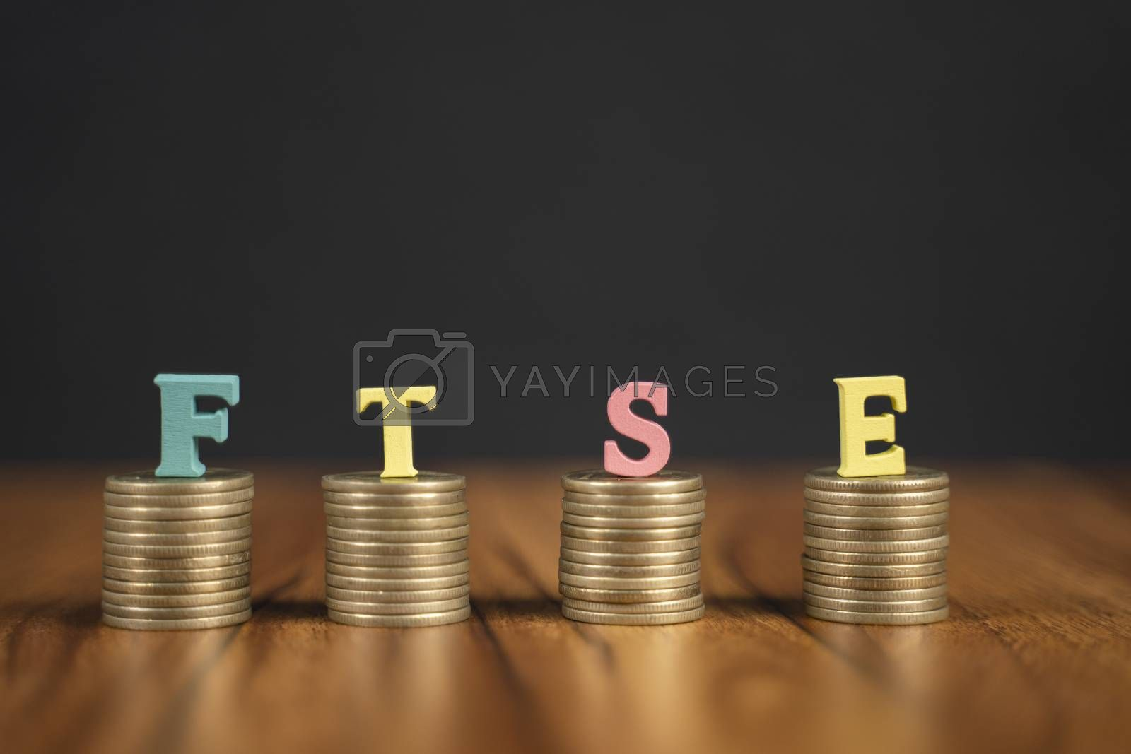 Concept of FTSE or Financial Times Stock Exchange showing with coins and letters on black background