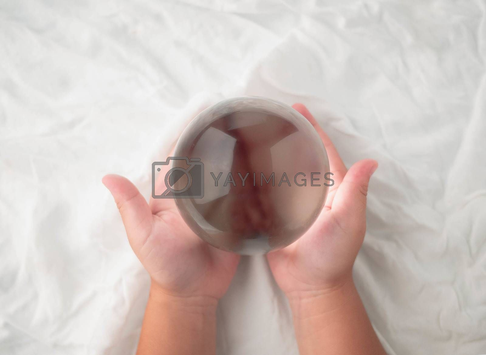 Hand holding a crystal glass ball transparent on white fabric background.