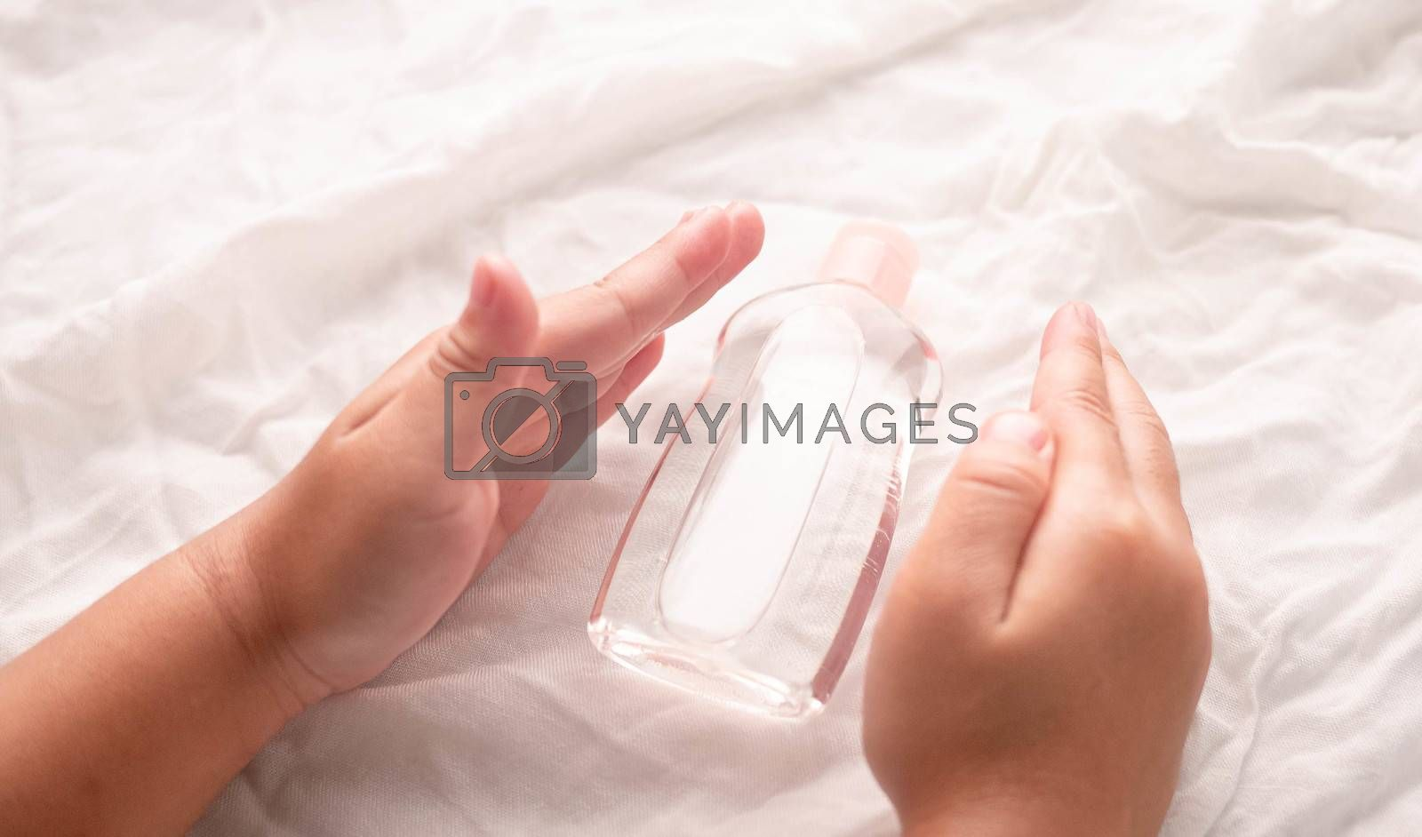 Close-up of Little hands holding transparent plastic bottle of oil on white fabric background. Care about soft body baby skin.