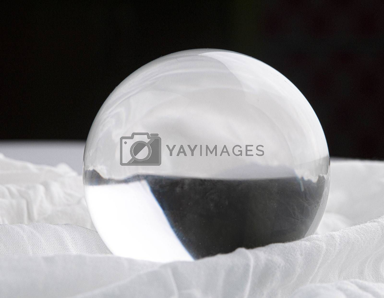 Crystal glass ball sphere transparent on white fabric and dark background.