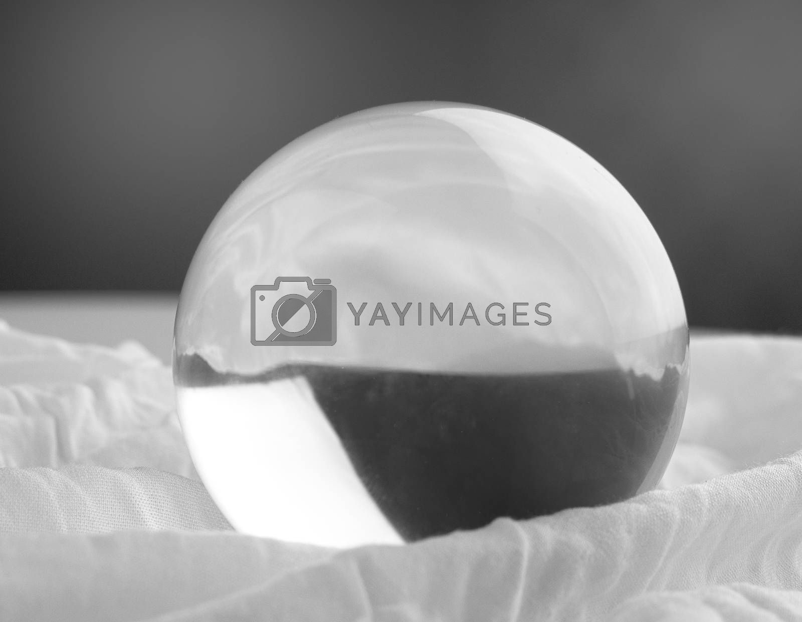 Crystal glass ball sphere transparent on grey gradient background.