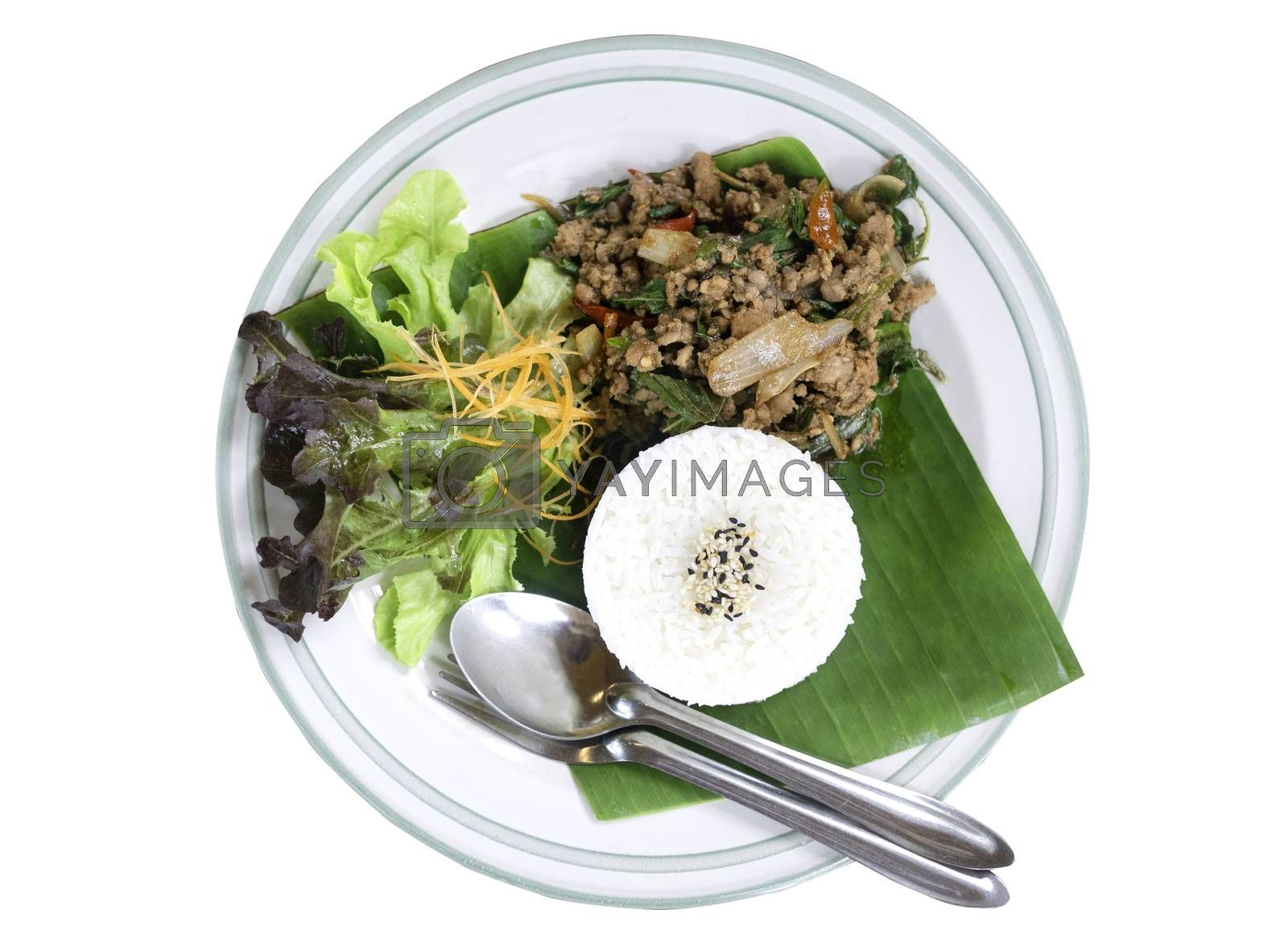 Thai food rice topped with stir fried pork and basil served with vegetables isolated on white background. top view.