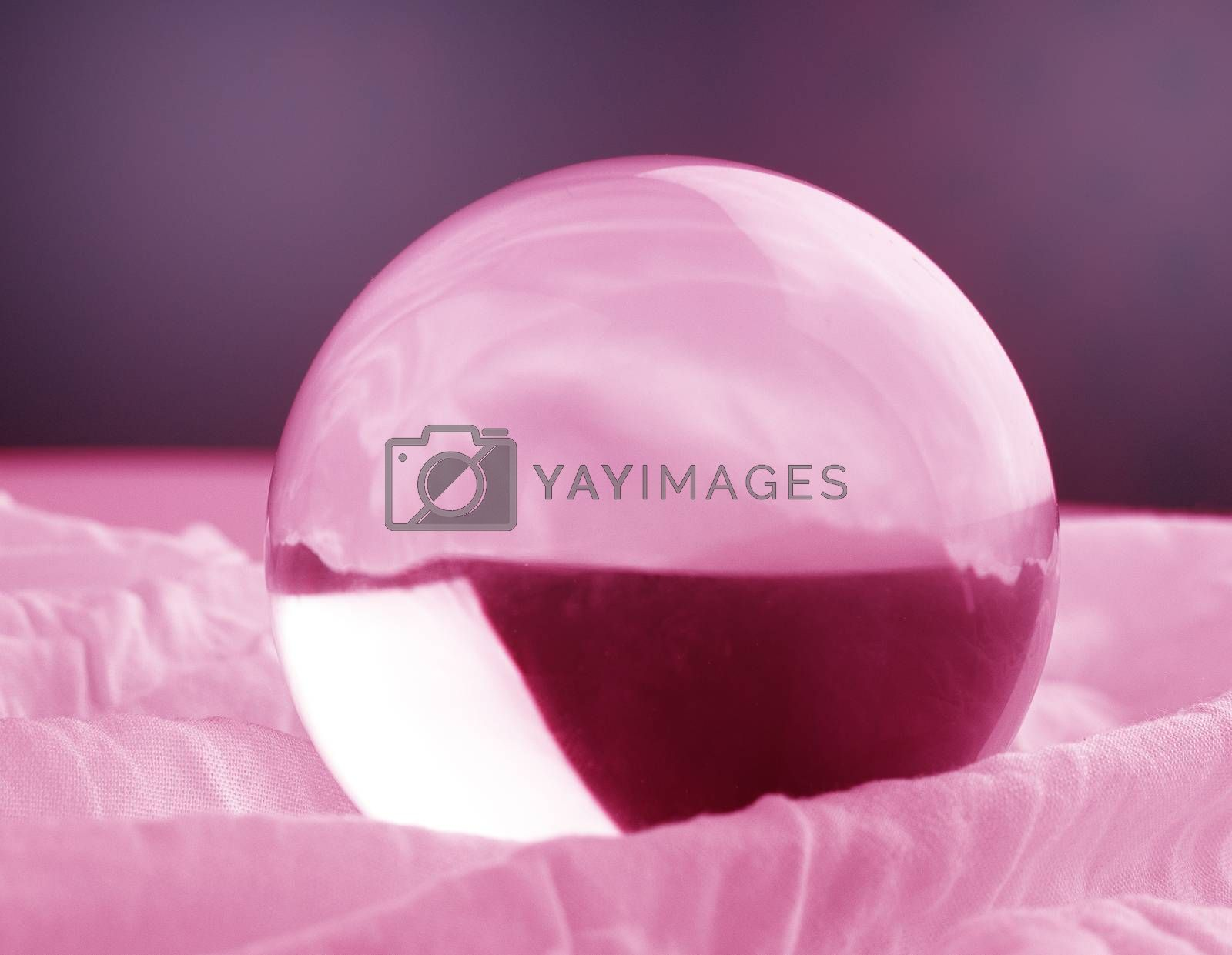 Crystal glass ball sphere transparent on pink gradient background.