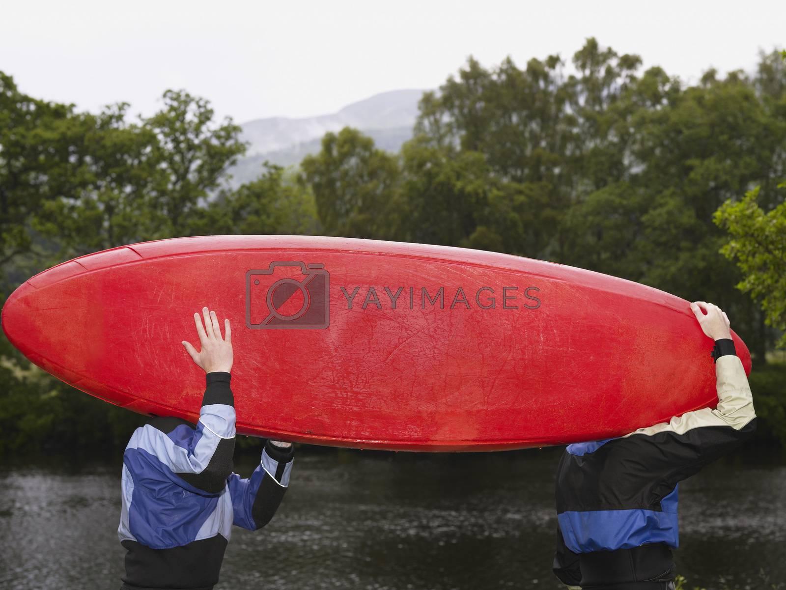 Two men carrying kayak outdoors