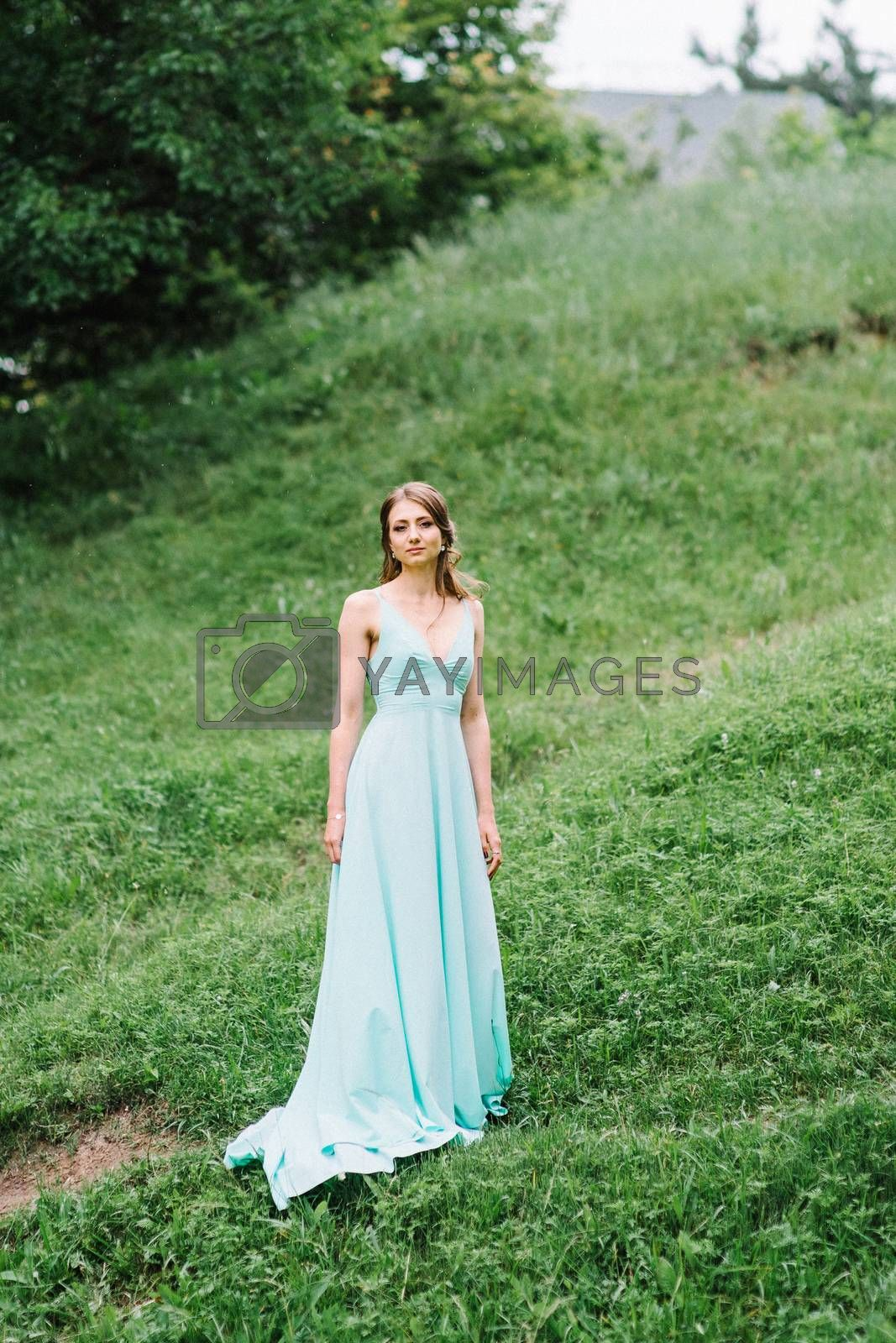 Happy girl in a turquoise long dress in a green park on a background of herbs, trees and rose bushes