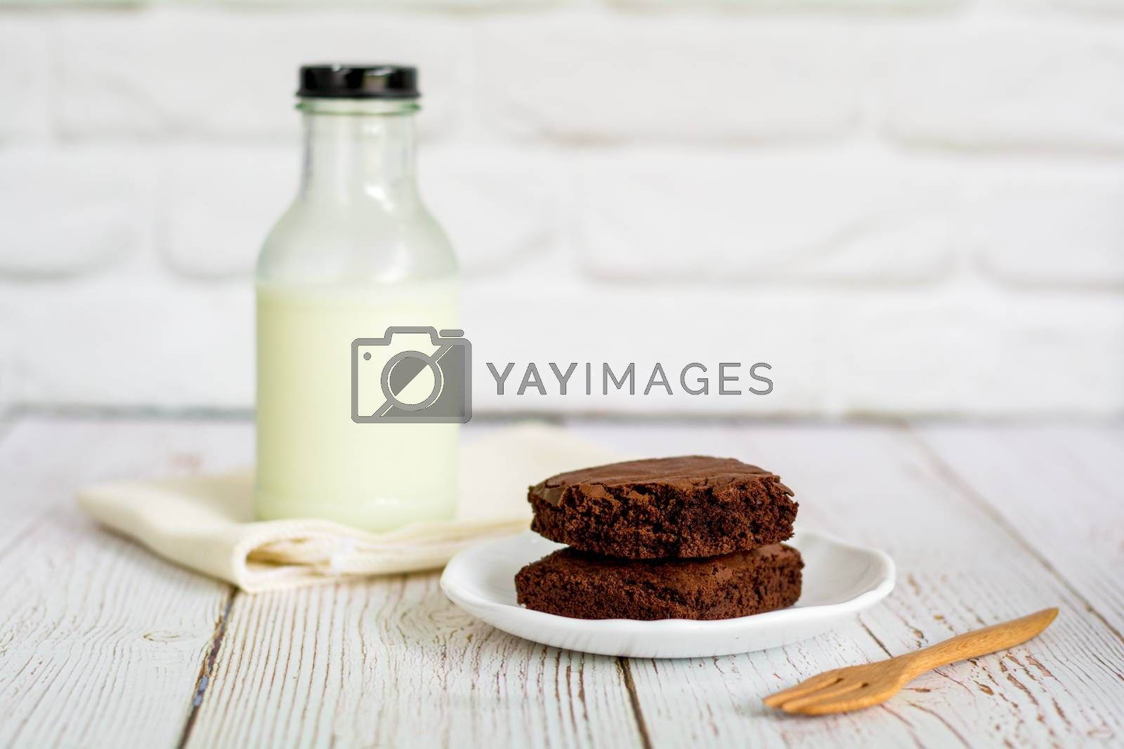 Piece of brownie cake on white small plate with bottle of fresh milk on wooden table and with brick wall with copy space.